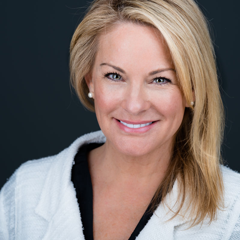 A blonde haired woman smiles contently during her professional headshot session