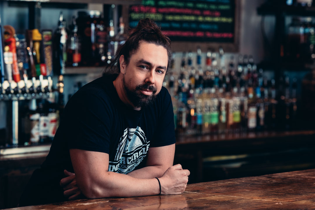 Bartender leans on the bar while looking at the camera for a company headshot