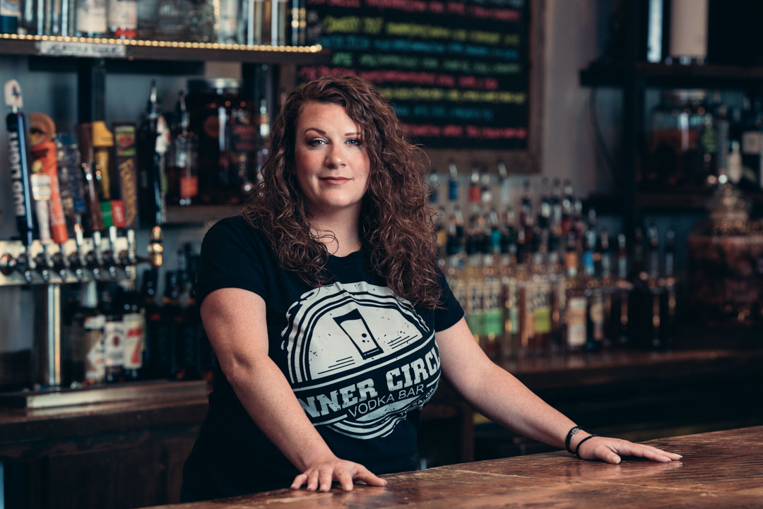 A business portrait of a female bartender standing confidently with both hands on the bar and raising an eyebrow
