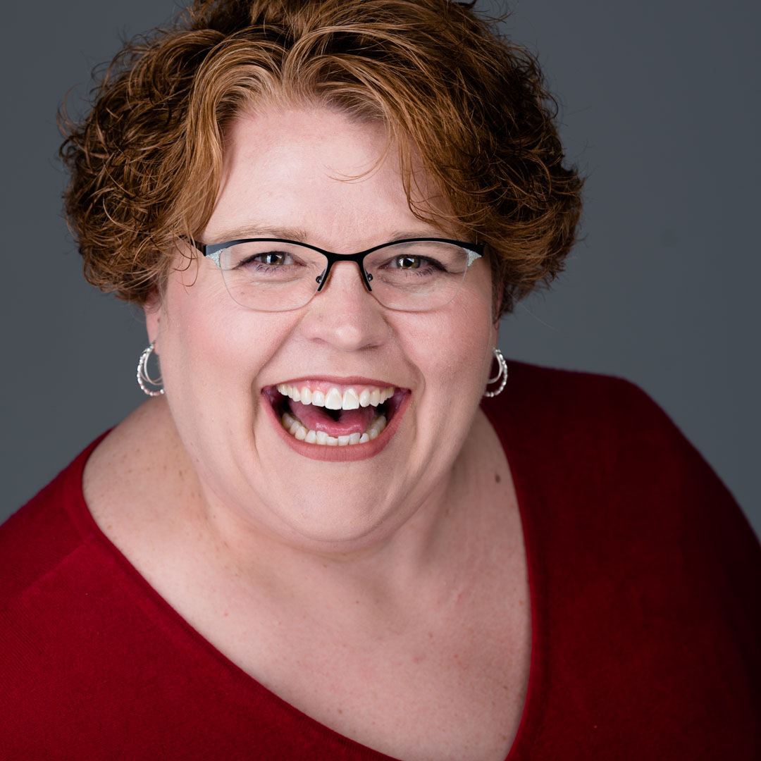 Women with red shirt, glasses, and short curly red hair laughs during her headshot session