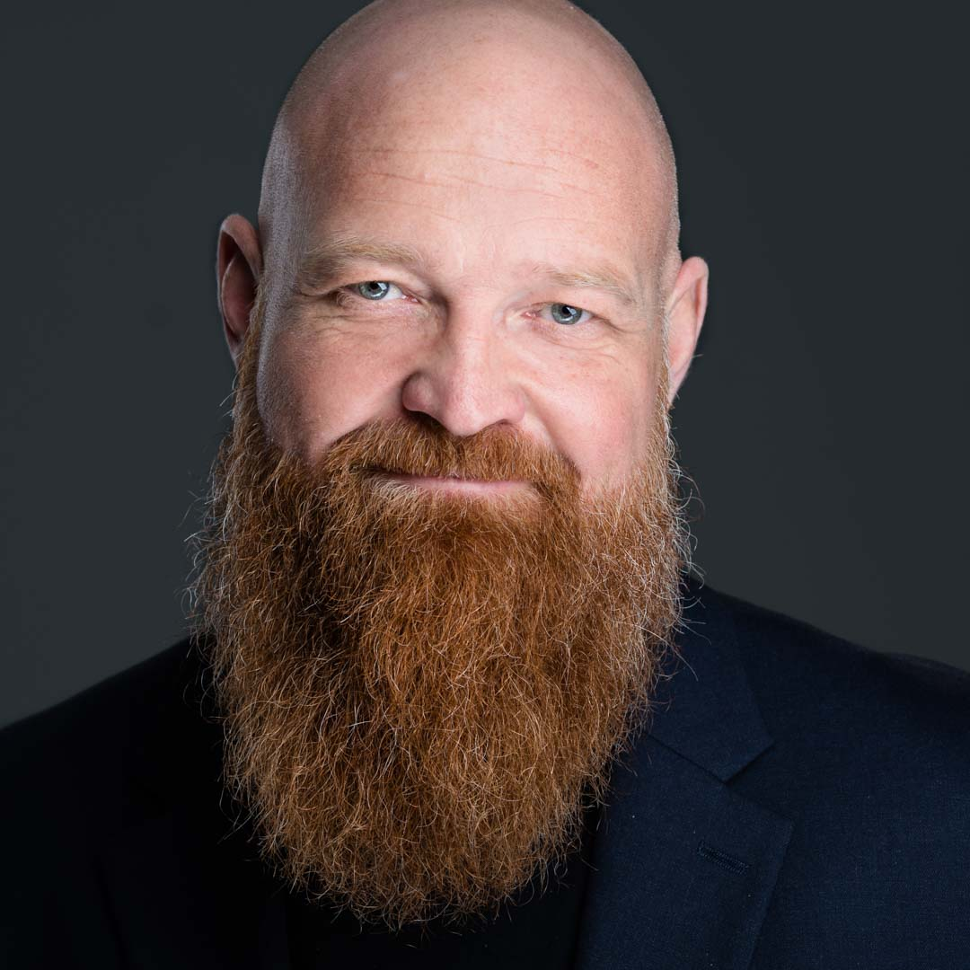 A bald man with a large beard grins confidently for one of his headshots