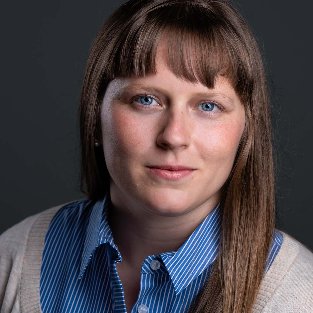 A girl with bright blue eyes, a blue striped shirt and a cardigan looks content in her business portrait