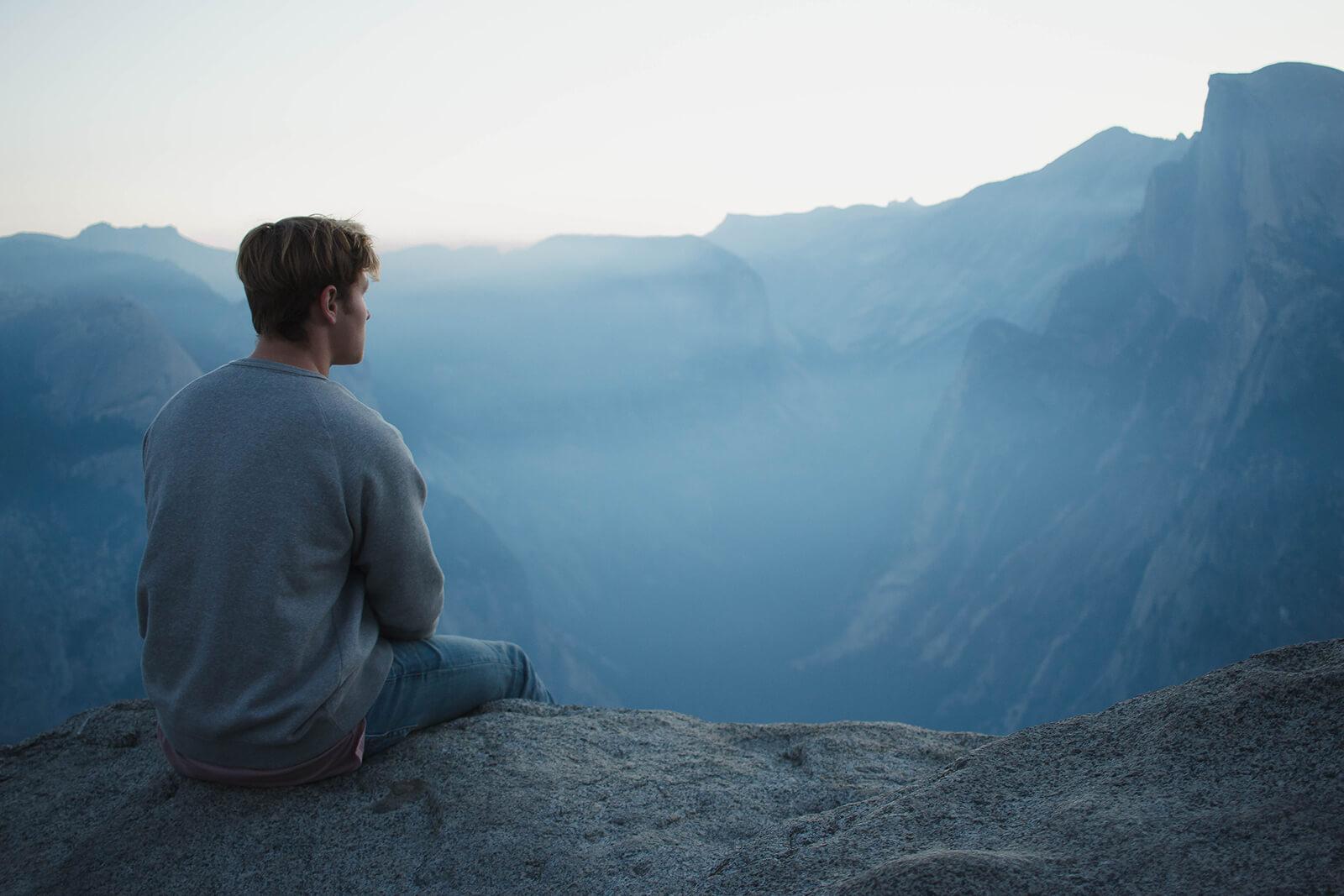 Man meditating on a clifftop