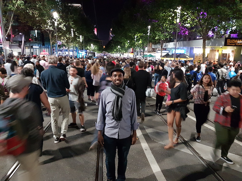 Awale is facing the camera. He is standing in the centre of the tram tracks in a Melbourne city street. It is night time. The area is brightly lit. Crowds of people fill the street and walk around Awale who is standing still.