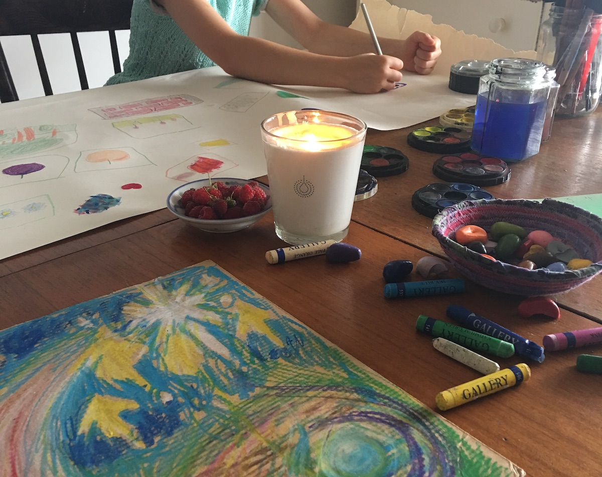 A colourful abstract drawing made with crayons on cardboard is in the foreground. It is on a table that holds crayons, bowls of fruit and coloured pebbles, a lit candle, and watercolour painting materials. A child's arms can be seen  in the picture. The child is drawing on a large page that already contains small colourful drawings across it.