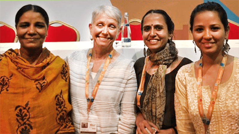 Four women stand together and smile at the camera.