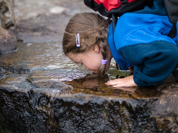 Picture of girl drinking water in the stream