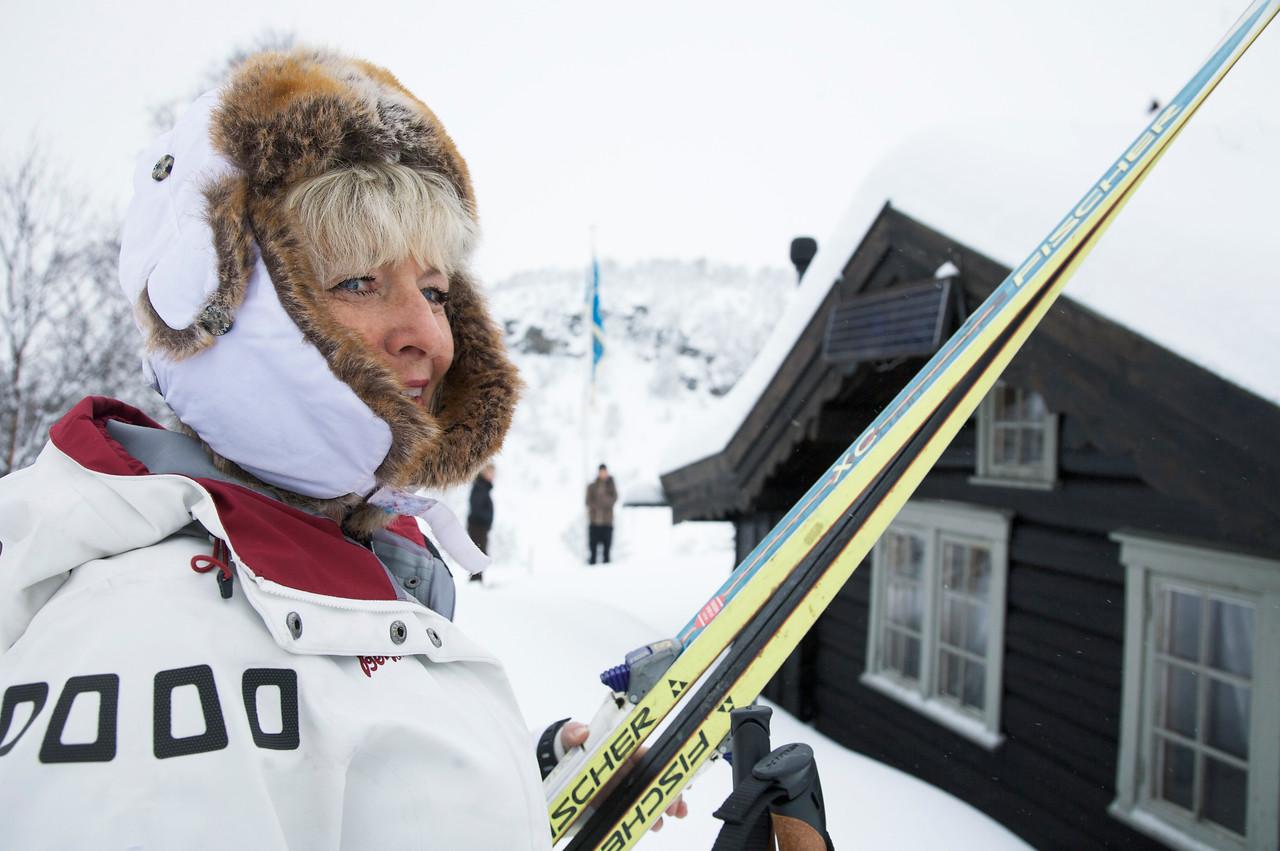 Dame med ski utenfor hytte
