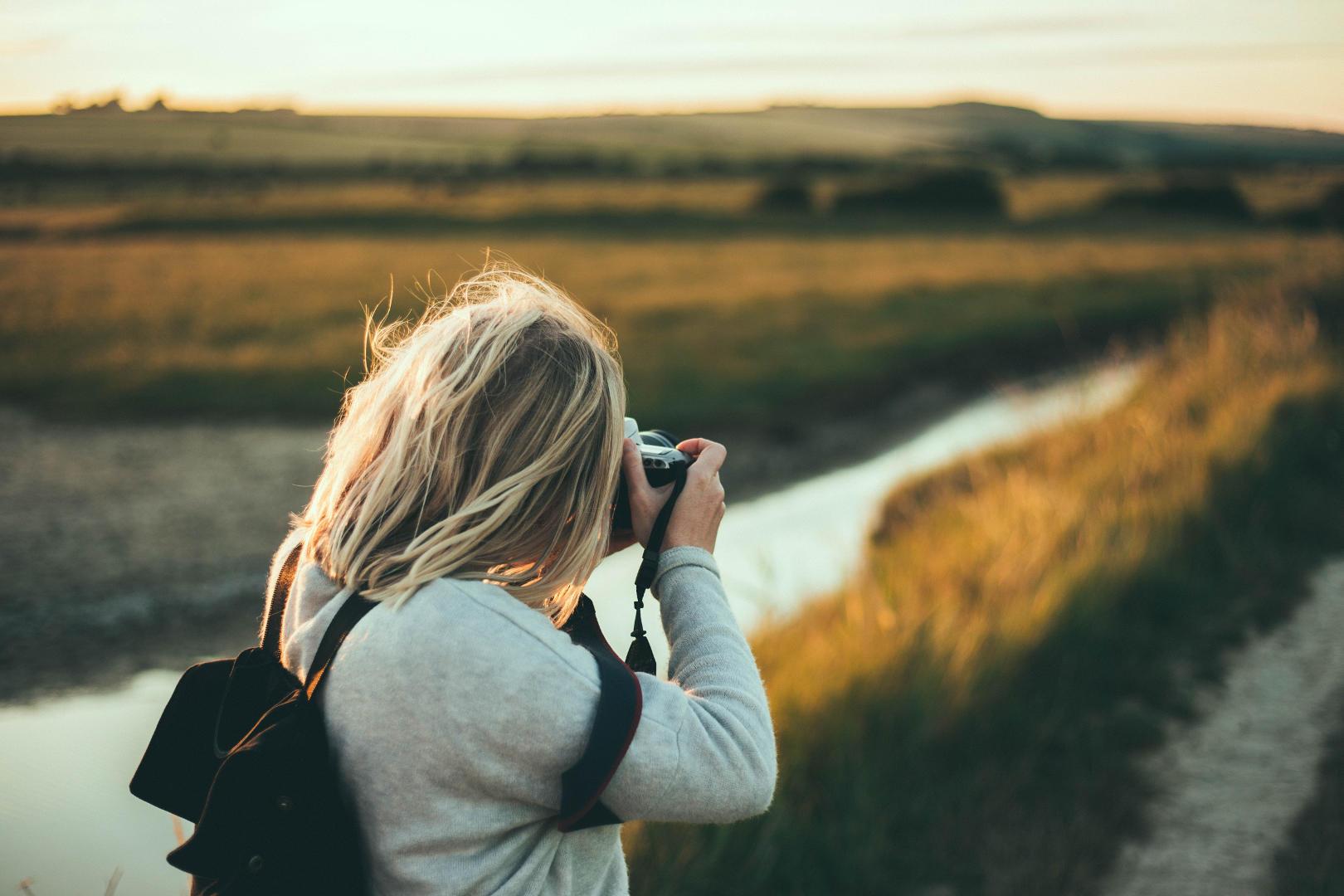 Eine Frau fotografiert einen Fluss.