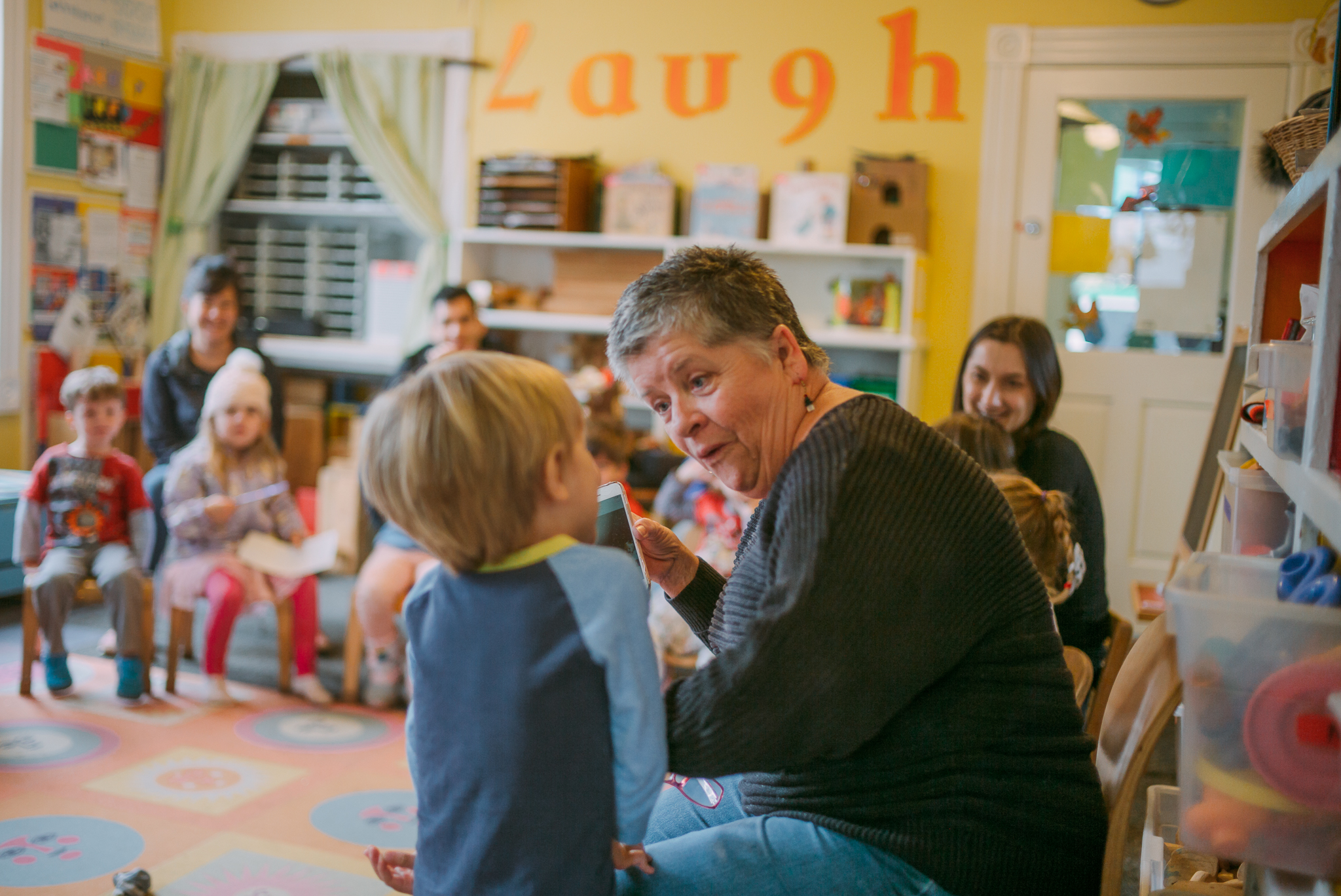 Teacher Pammi interacts with a student during show and tell at the Cottage.