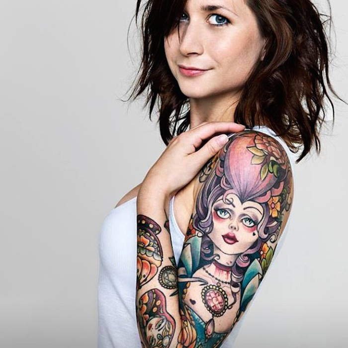 A young woman with a colourful full sleeve tattoo and shoulder length brown hair