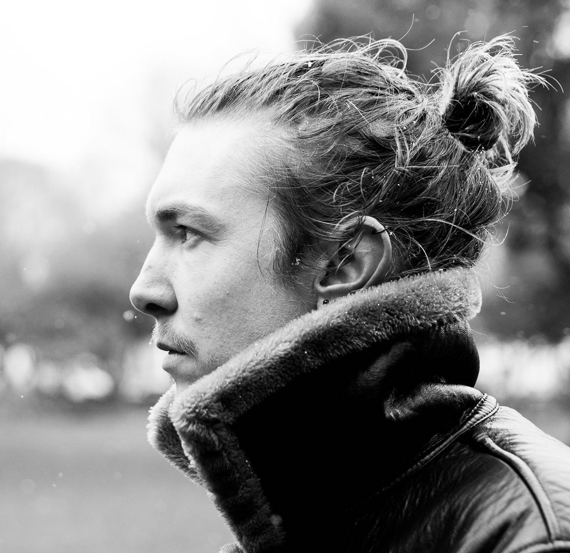 Remayn: a white man with long hair tied back in a bun, wearing a thick coat