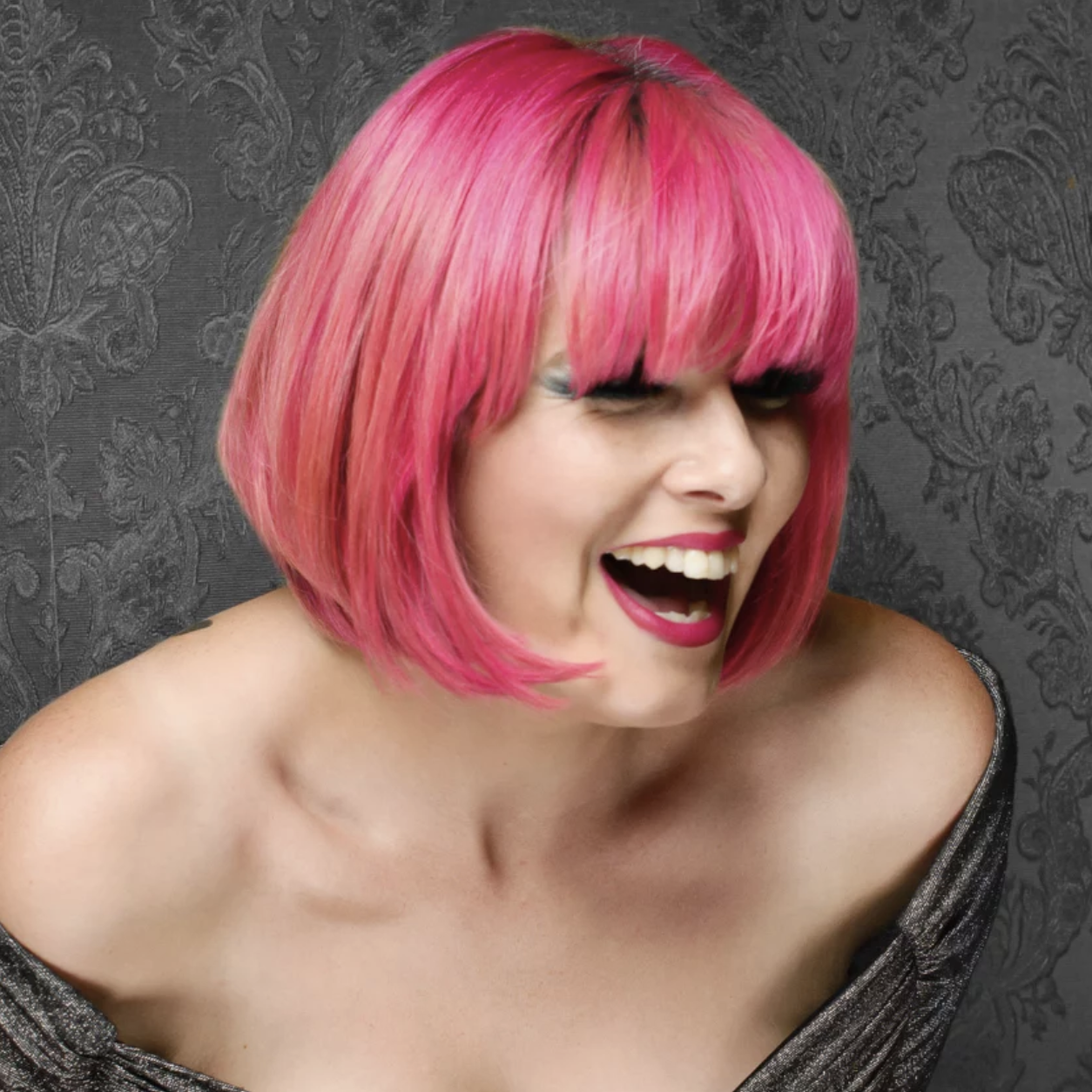 A young white woman with a hot pink bob cut, laughing