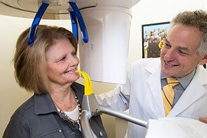 Dr. Burden smiles at female patient standing in cone beam scanner