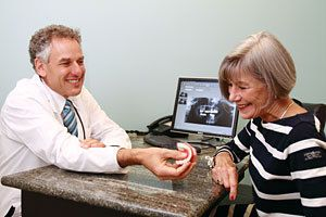 Dr. Burden sits behind desk and hands denture to woman in a black-and-white striped shirt