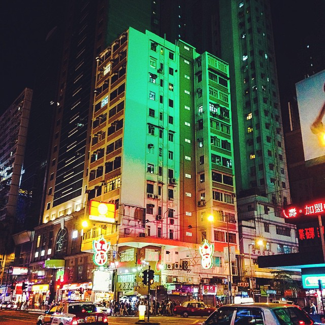Green glowing corner elevation of a street in Hong Kong at night