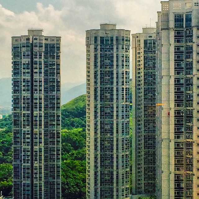 Cluster of vertical housing towers set within a mountain forest in Hong Kong