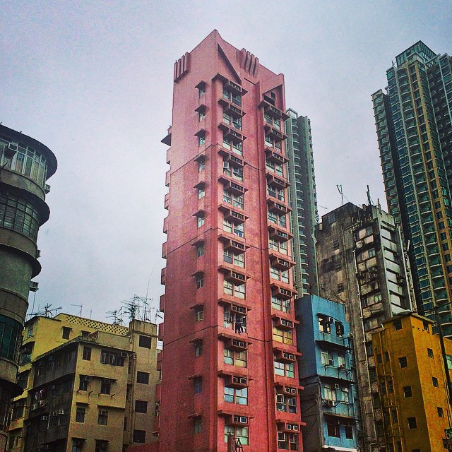Skinny pink tower paired with blue and yellow buildings in Hong Kong