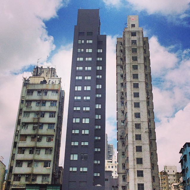 Three monochrome towers set against a cloudy blue sky in Hong Kong
