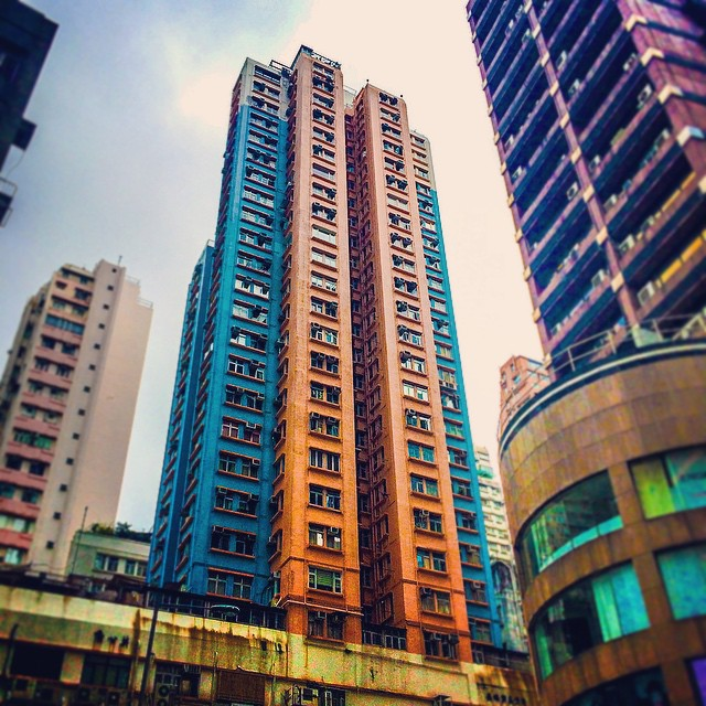 Orange and blue tower viewed from the street in Hong Kong