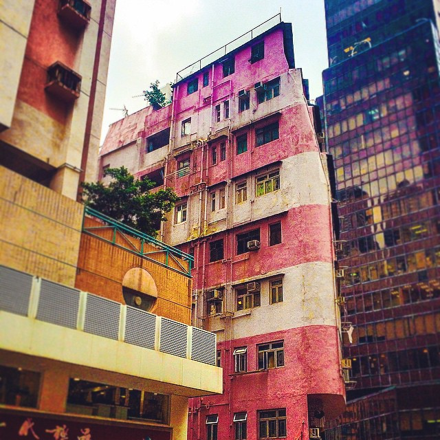 A white and pink striped building at the corner of a street in Hong Kong