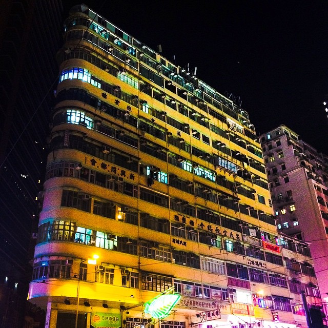 Corner slab building of housing lit from the street below at night in Hong Kong
