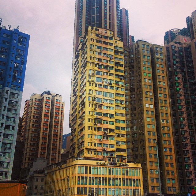 Yellow tower and podium building set against the dense city of Hong Kong