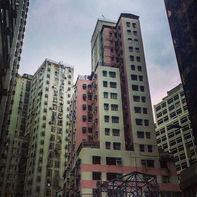 Pink and white building with alternating stepping towers on a podium block in Hong Kong
