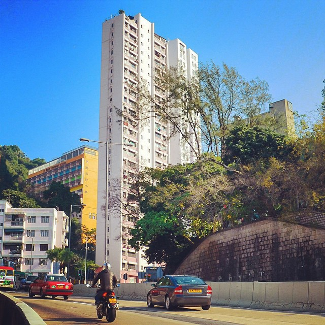 Skinny white tower slab next to the highway in Hong Kong