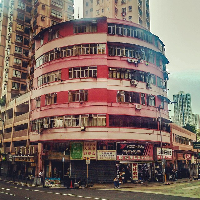 Rounded pink corner building above a shop in Hong Kong