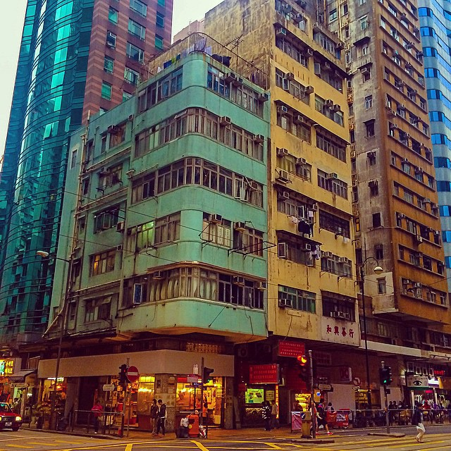 Paired blue and yellow buildings on a street corner in Hong Kong