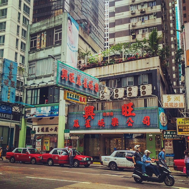 Building with large signage and a roof garden above the street in Hong Kong