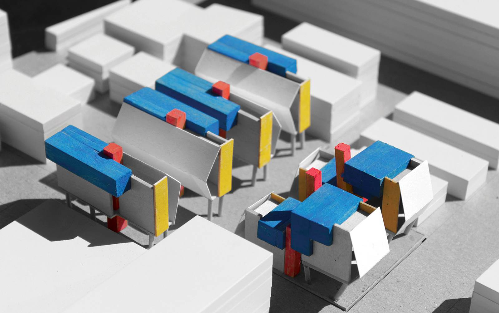 Model photo of the proposed massing scheme for QTCT housing diagrammed with color coded material concepts