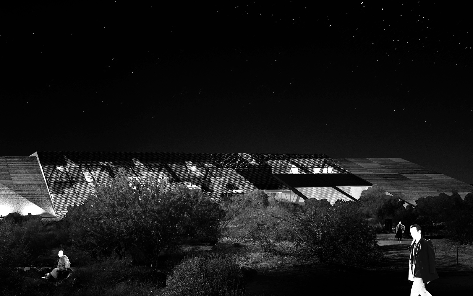 Perspective of the desert wash landscape with visitor trail in front of the glowing RACA gallery extension at night