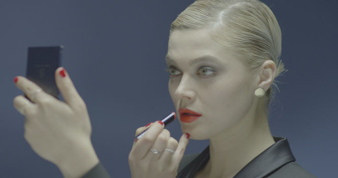 an intense model with a sharp coiffure applying red lipstick