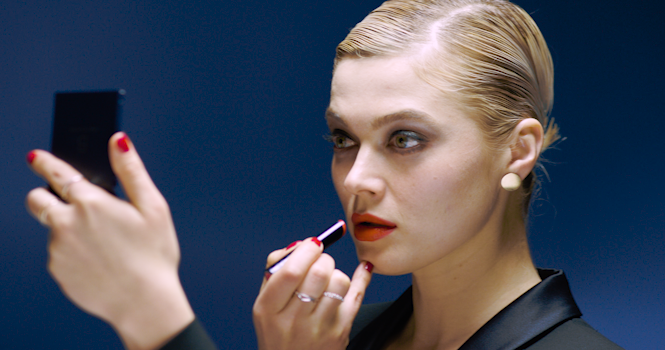 an intense model with a sharp coiffure applying red lipstick, but color-corrected