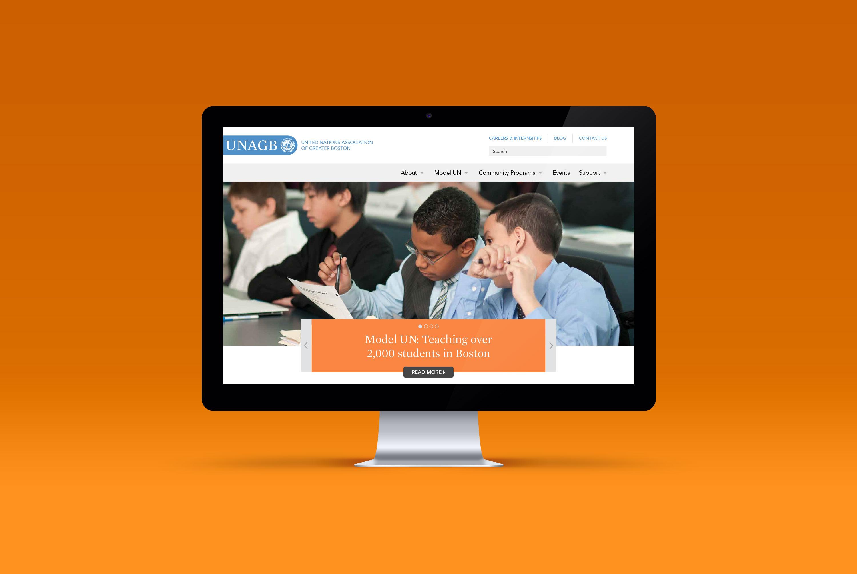 UNAGB website homepage on iMac display with orange background