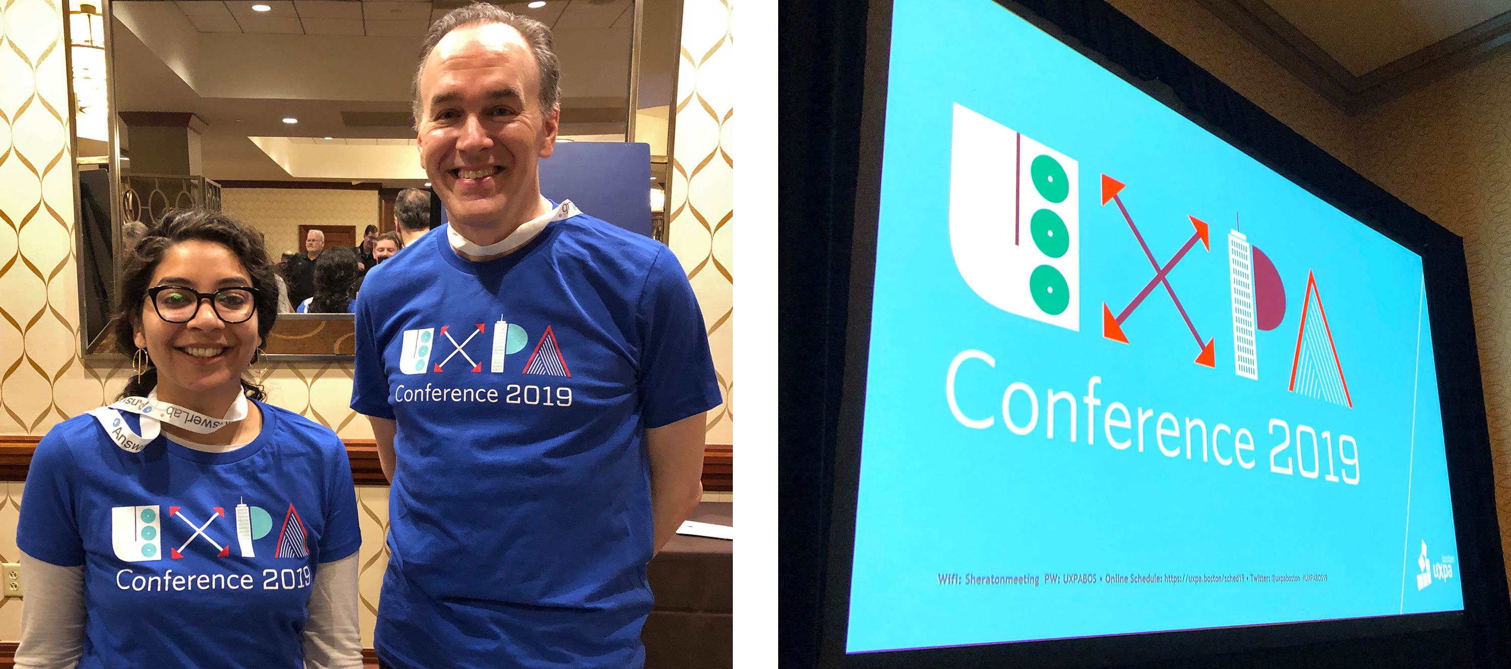 Two people wearing UXPA conference t-shirts at the UXPA Boston Annual conference. A large screen displays the UXPA Conference 2019 logo.