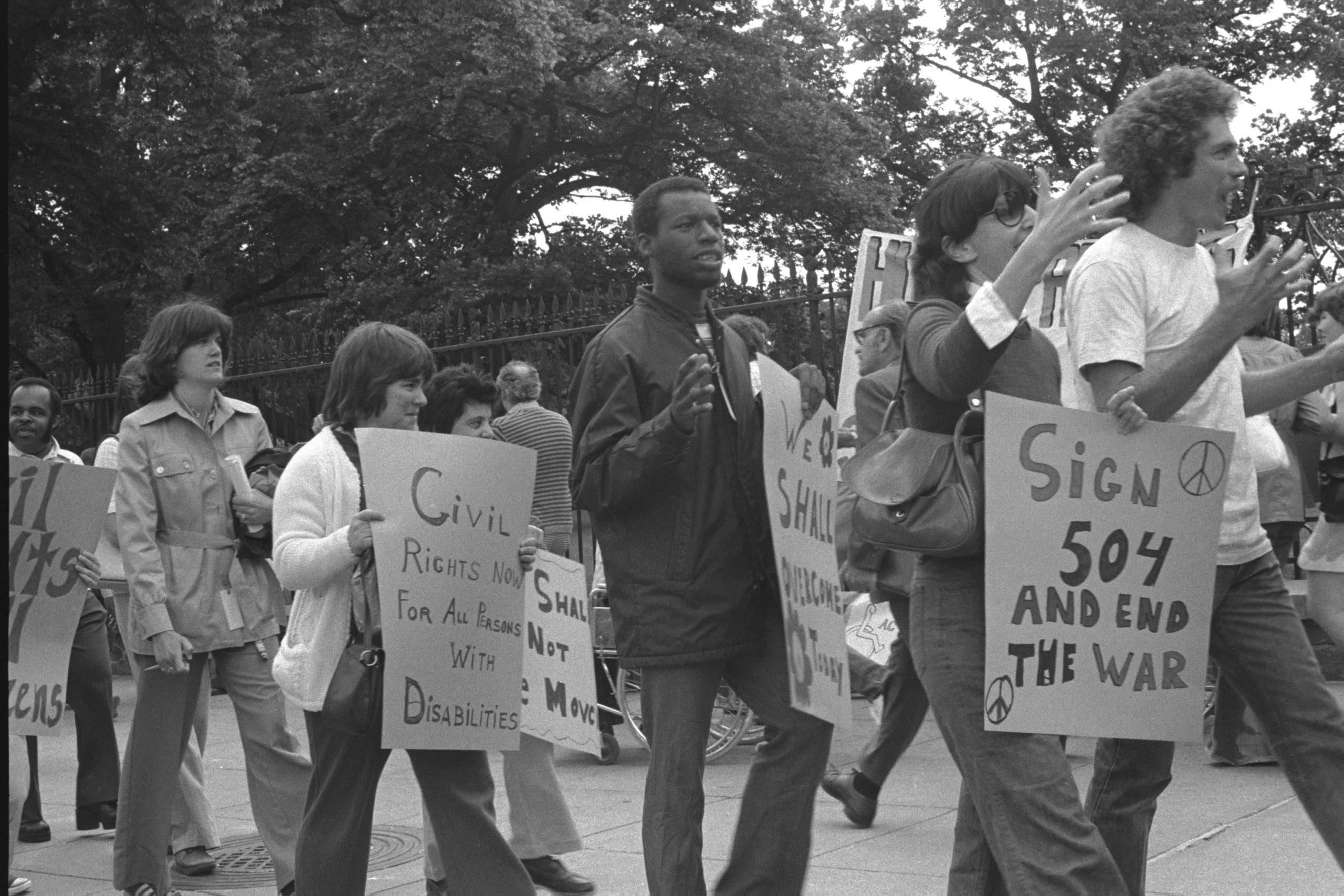 Personas manifestándose con carteles en lucha por los derechos de las personas con discapacidad para la toma de favor de la sección 504 en Estados Unidos. Las personas están manifestandose pacificamente con carteles que dicen: Derechos civiles ahora para todas las personas con discacapcidad, sección 504 y fin de la guerra...