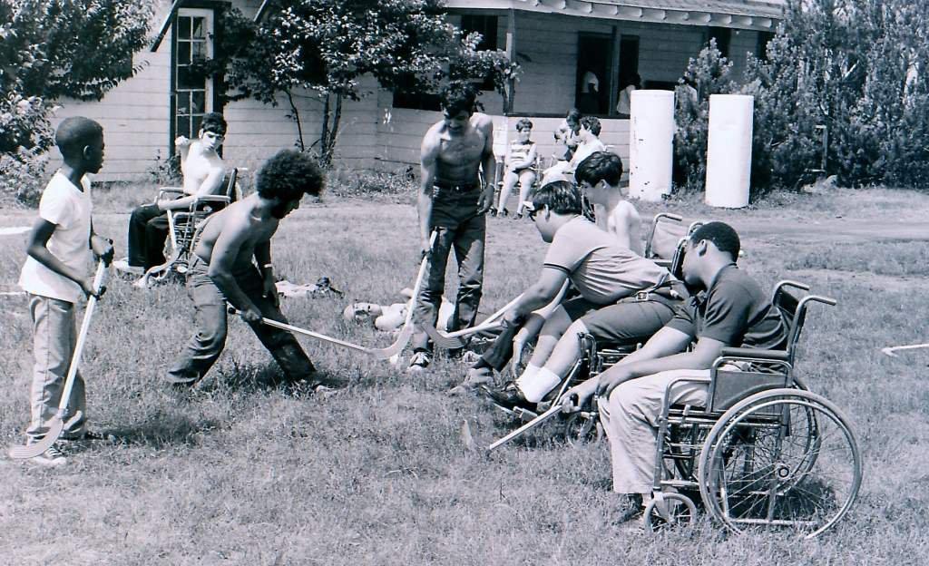 Diversidad en estado puro. Adultos y adolescentes, con y sin discapacidad, negras y blancas, jugando al hockey sobre la hierba del campamento. Un ejemplo de inclusión y toda una declaración de intenciones en plena decada de los 70.