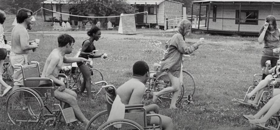Una imaen del campamento Jened, una monitora está realizando una actividad y está en el centro de un círculo formado por personas con discapacidad en silla de ruedas. Todos parecen estar emocionados y divirtiéndose.iendose.