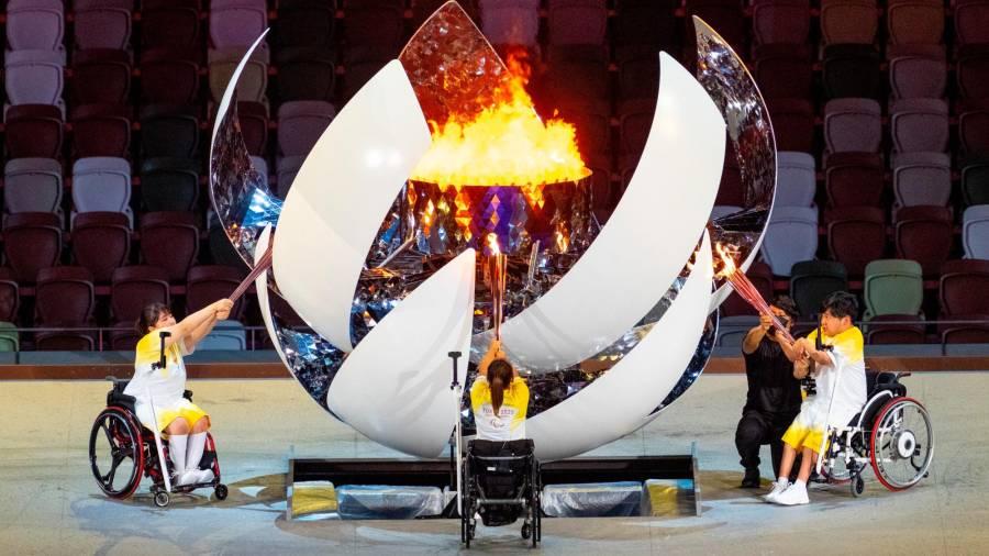 Los deportistas Yui Kamiji, Shunsuke Uchida y Karin Morisaki encienden a la vez la antorcha olímpica. Los tres van en silla de ruedas y cada uno de ellos está colocado en un lateral de la gran esfera.