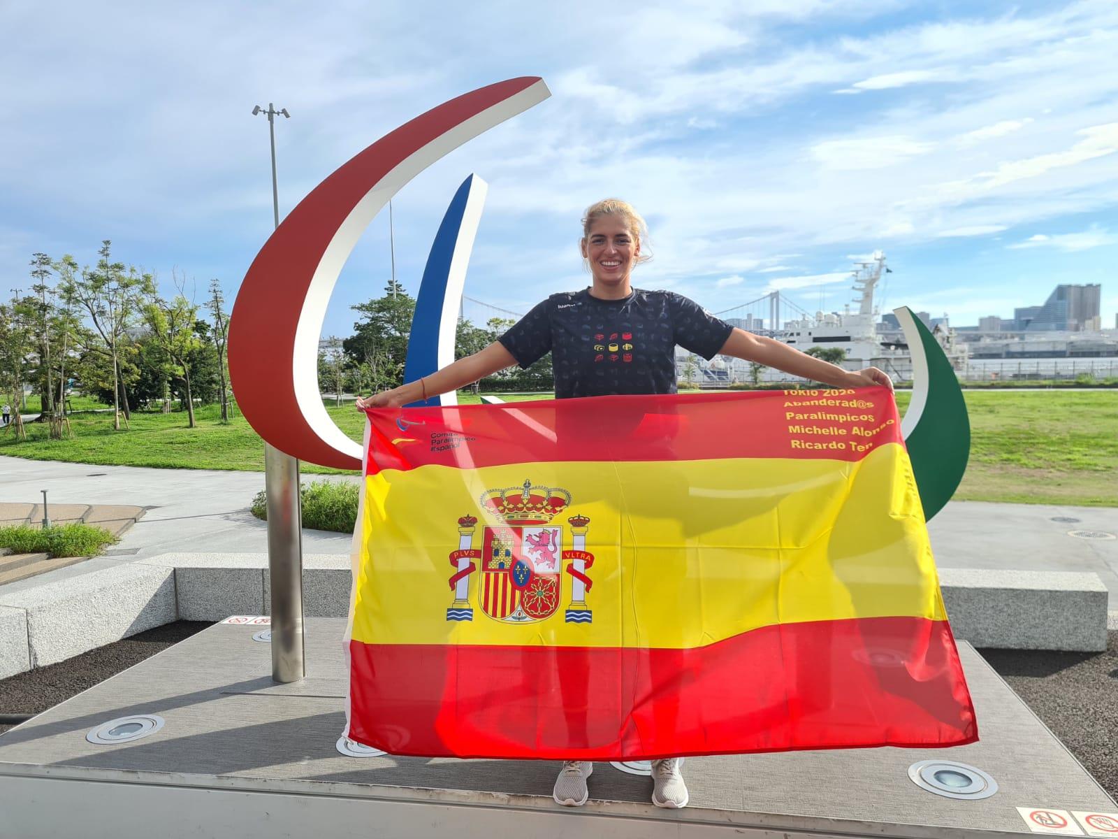 Michelle Alonso en Tokio posa frente al símbolo paralímpico mientras sonríe mostrando la bandera de España.