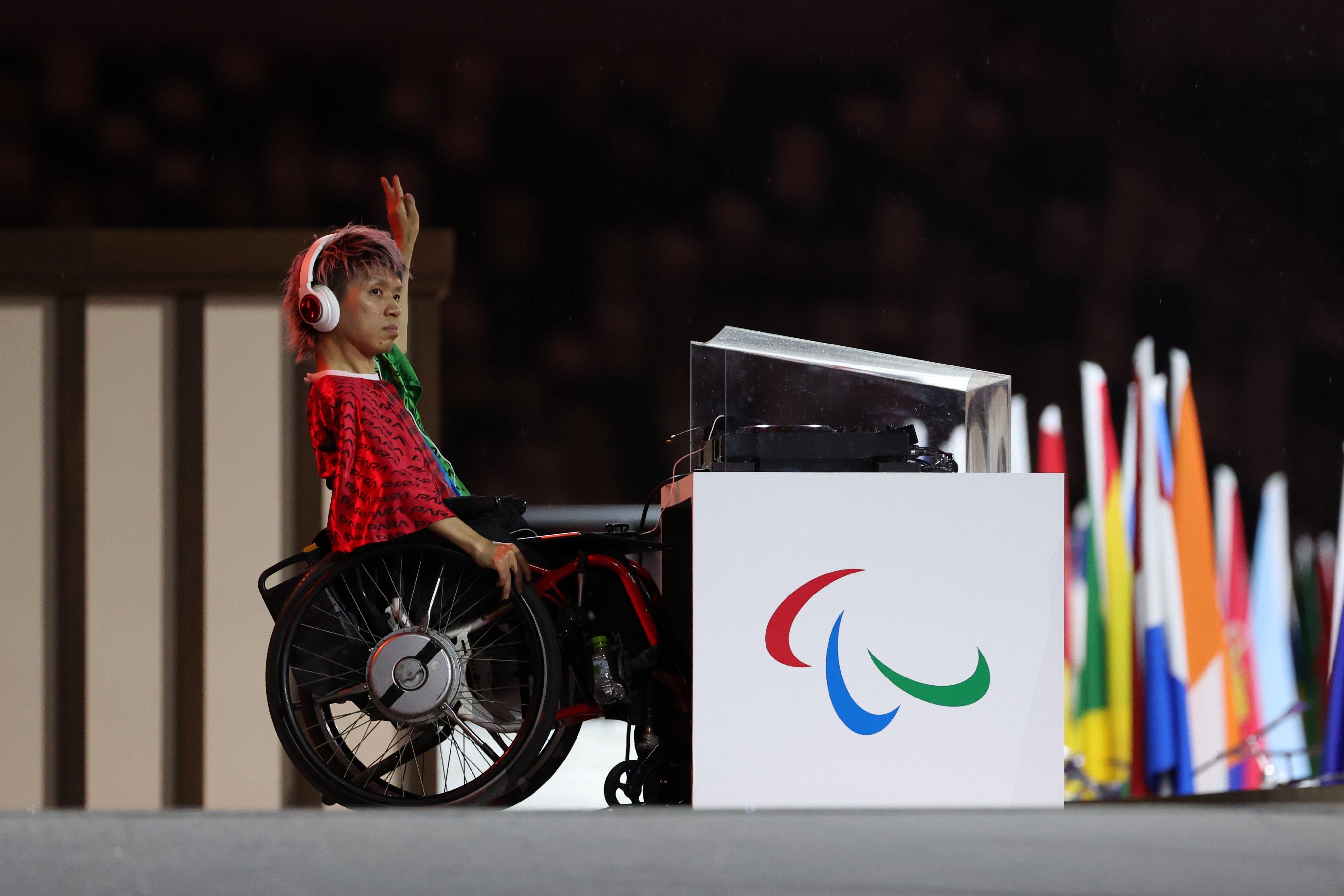 El dj Keita Tokunaga en la ceremonia inaugural. Aparece en su silla de ruedas y tiene a su lado su equipo de dj. Está levantando la mano para saludar.