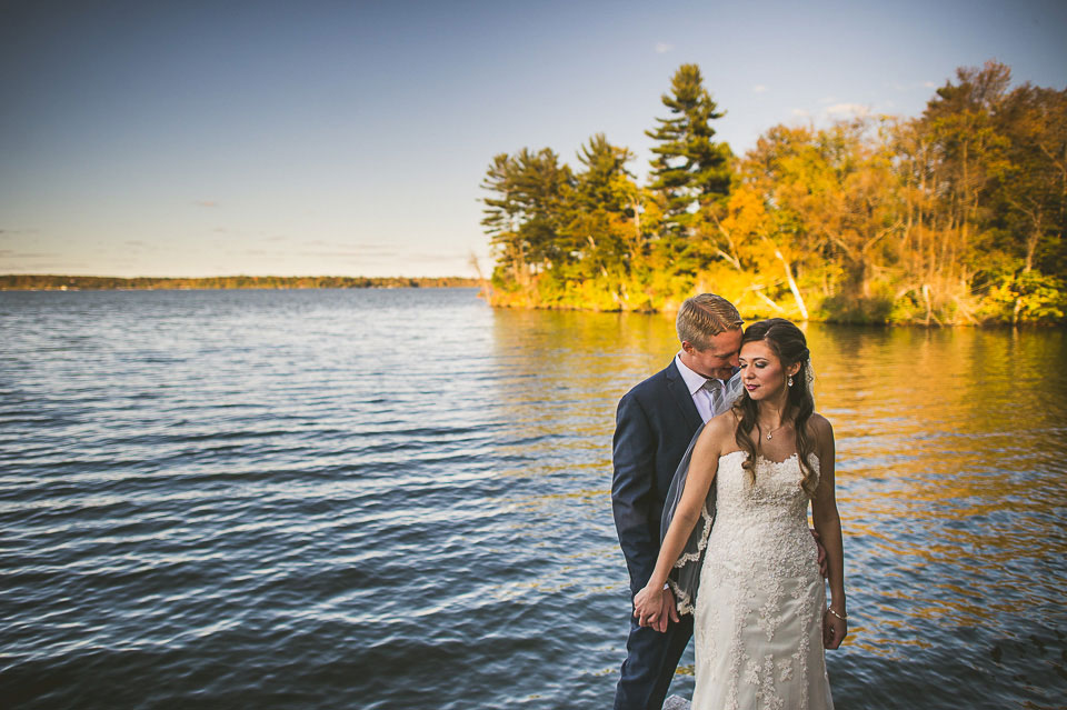 Bride and groom holding hands near a lake