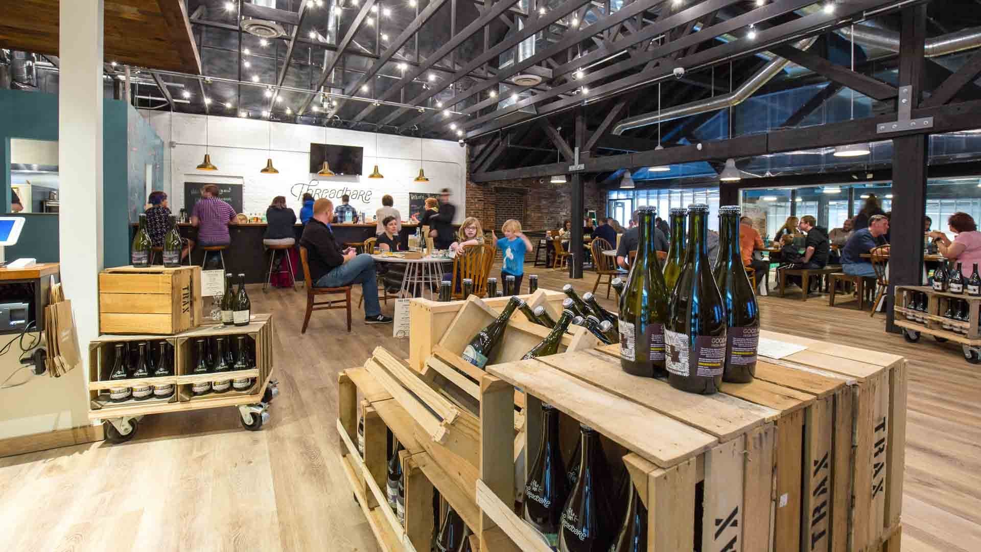 customers at tables and wine on display in Threadbare Cider & Mead