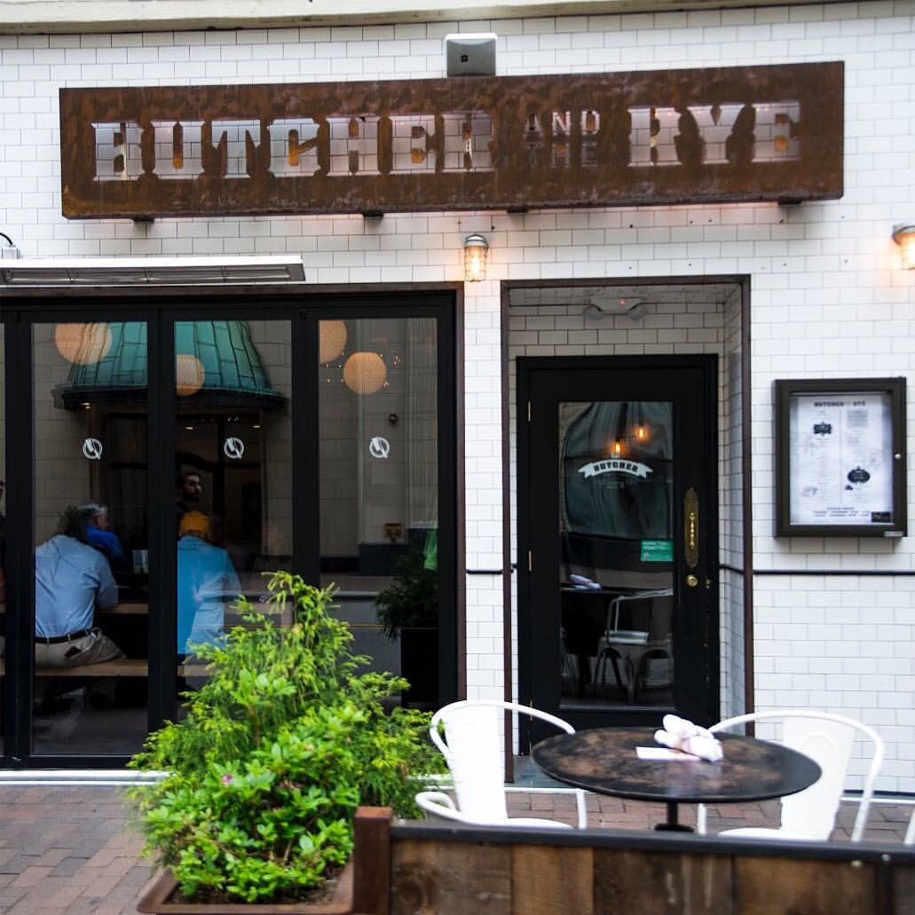 The outside of Butcher and the Rye is featured, with some tables and a plant