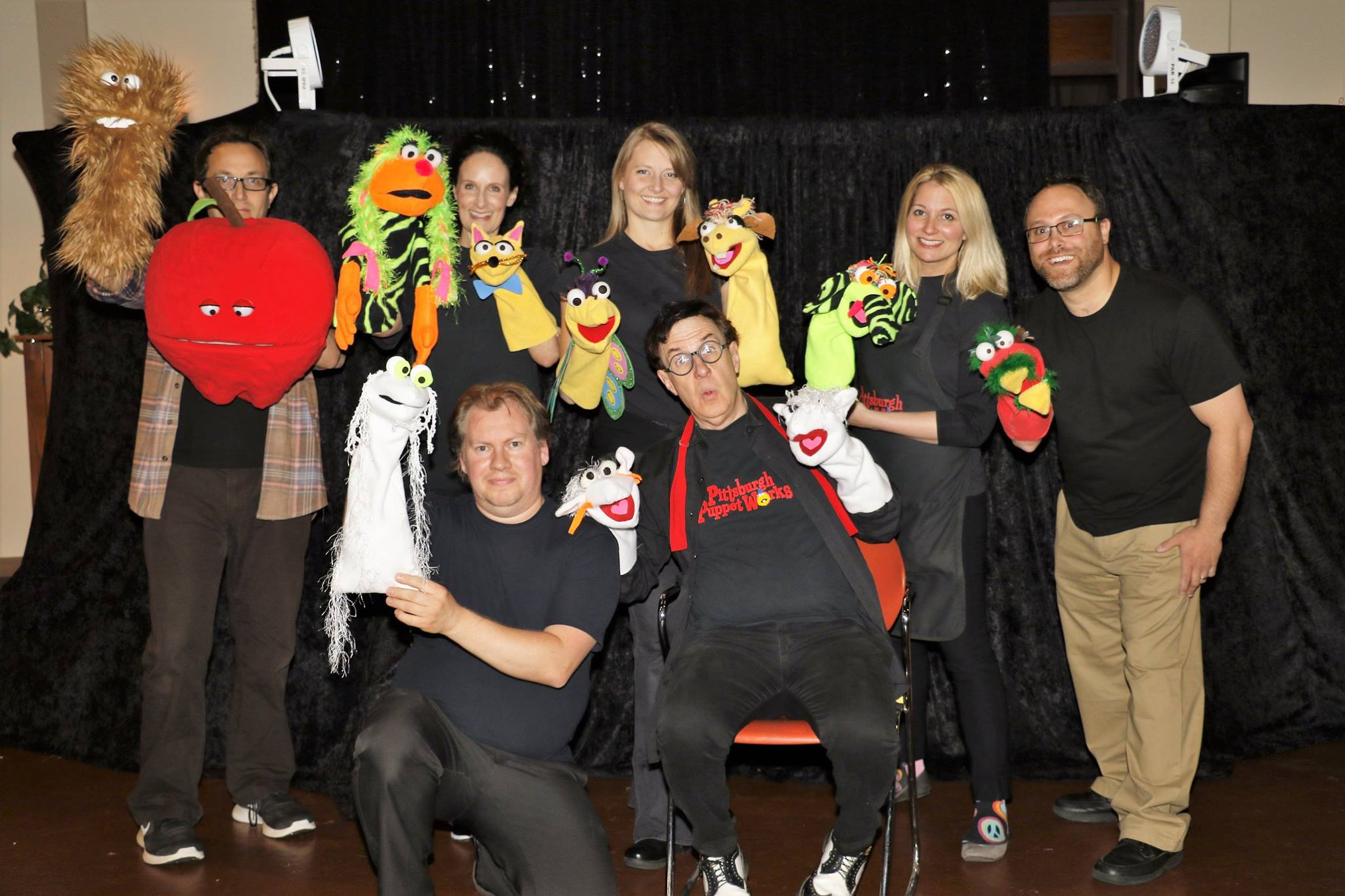 workers of Pittsburgh Puppet Works holding puppets behind-the-scenes of party