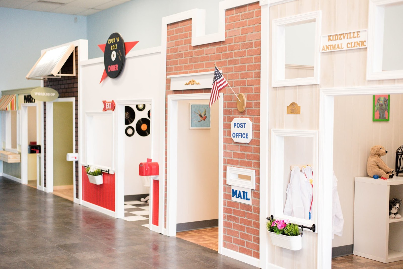 A picture of the inside of Kidzville; the post office, animal clinic and other pretend stores are featured