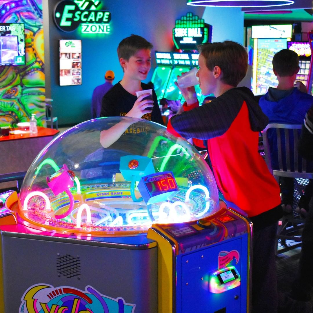 Two kids are playing arcade games at Zone 28
